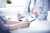 istock Doctor and  female patient sitting at the desk and talking  in clinic near window. Medicine and health care concept. Green is main color 1148334988