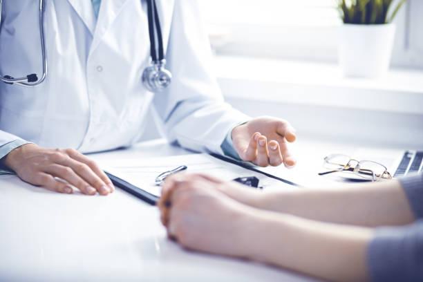Arzt und Patientin sitzen am Schreibtisch und sprechen in der Klinik in der Nähe des Fensters. Medizin- und Gesundheitskonzept. Grün ist Hauptfarbe – Foto