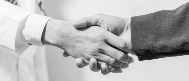 Arzt und ihr Anwalt Händeschütteln, schwarz / weiß – Foto