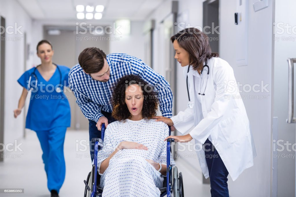 Doctor and man comforting pregnant woman in corridor stock photo