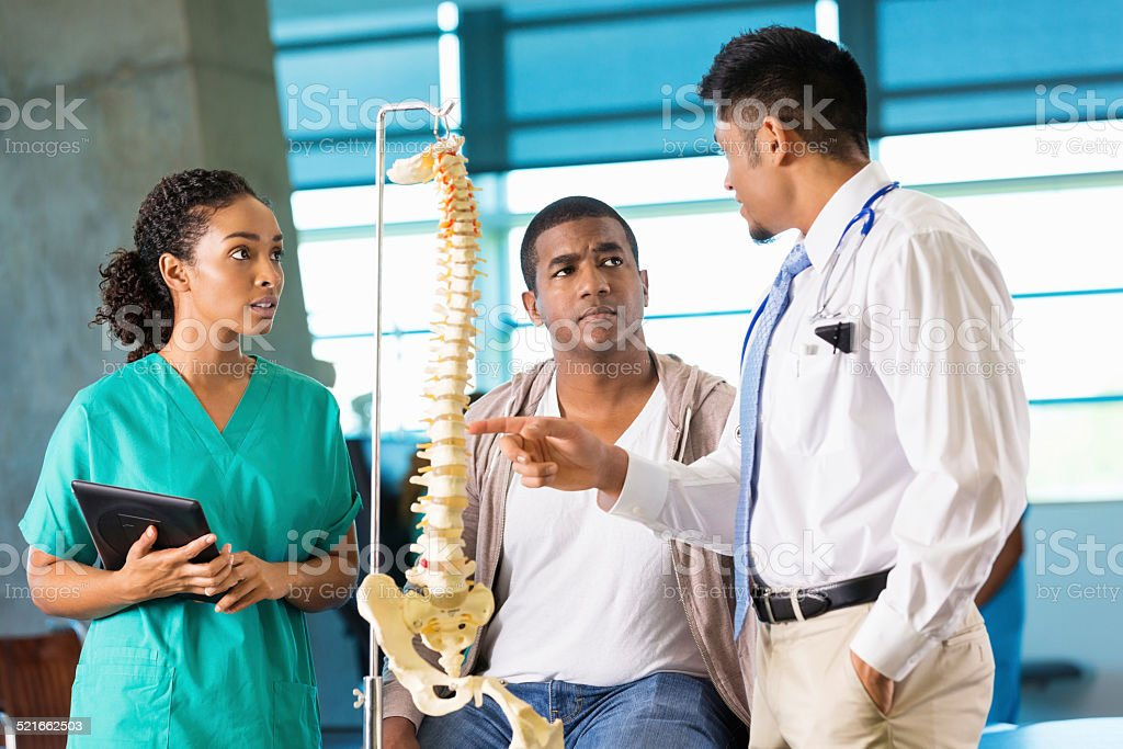 Doctor and nurse consulting with patient about back spine injury stock photo