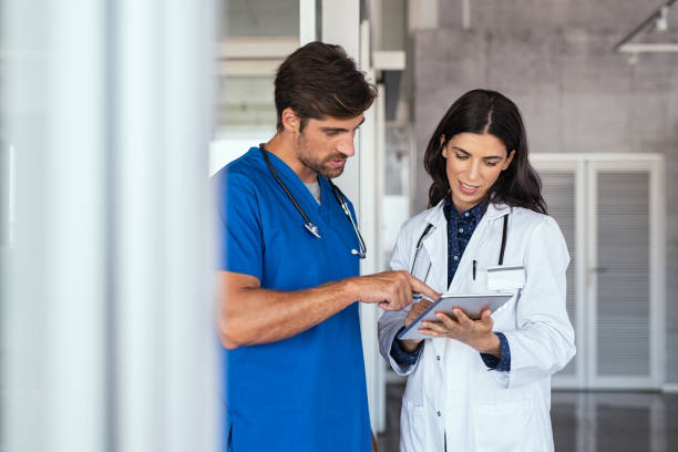 Doctor and nurse discussing report Doctor and nurse discussing over a medical report in hospital. Female mature doctor and nurse checking clinical report of patient online. Healthcare staff having discussion in a hallway of private clinic. assistant stock pictures, royalty-free photos & images