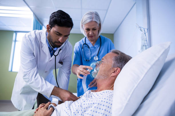Doctor and nurse examining a patient Doctor and nurse examining a patient in hospital oxygen mask stock pictures, royalty-free photos & images
