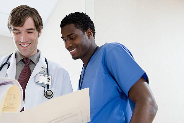 arzt und krankenschwester blick auf papierkram - assistent stock-fotos und bilder