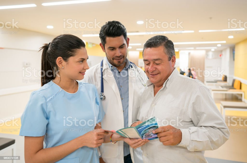 Doctor and nurse talking to a patient showing him a brochure all looking very happy stock photo