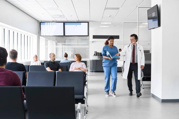 Arzt und Krankenschwester gehen an Patienten in der Lobby vorbei – Foto