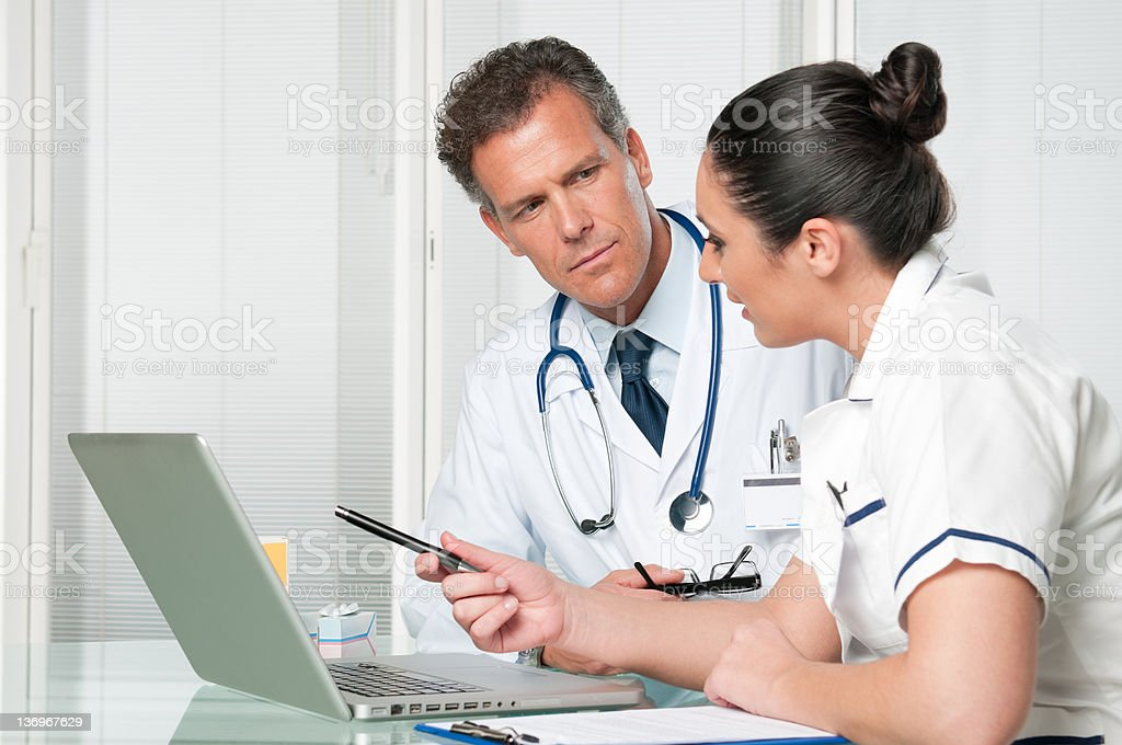 Doctor and nurse working at laptop royalty-free stock photo