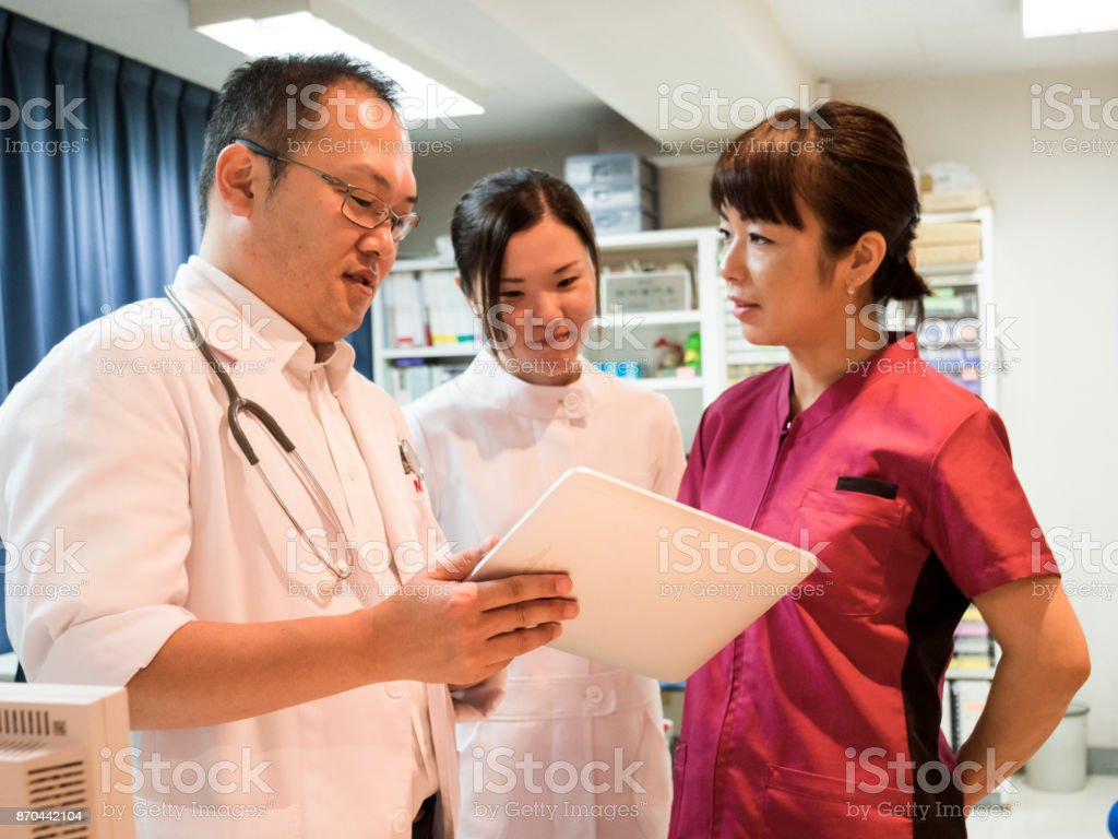 Doctor and nurses watching tablet. stock photo