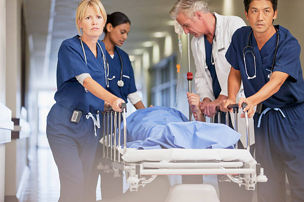 Doctor and nurses wheeling patient in gurney down hospital corridor stock photo