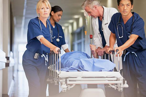 médico y enfermeras wheeling paciente en mesa de ruedas de hospital corri de - problemas fotografías e imágenes de stock