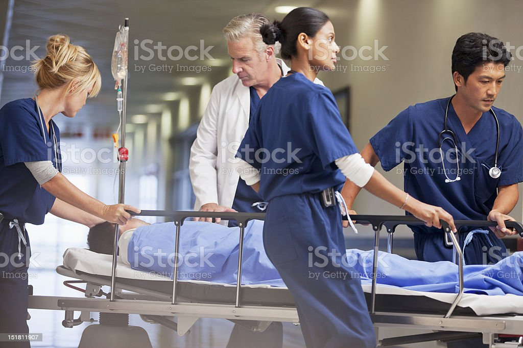 Doctor and nurses wheeling patient in gurney through hospital corridor stock photo