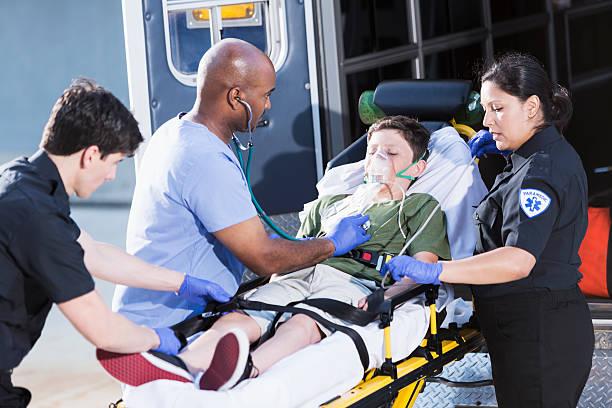 médecin à aider un enfant et auxiliaires médicaux - auxiliaire médical photos et images de collection