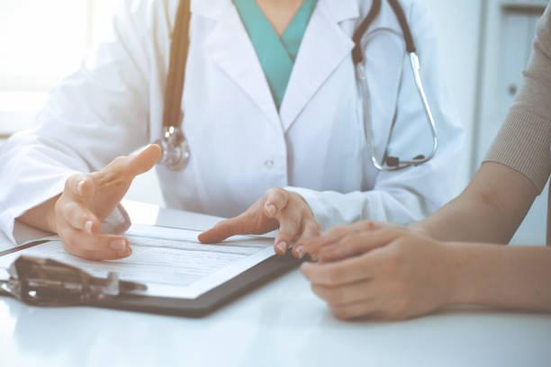 Arzt und Patient diskutieren in der Klinik über etwas, nur händer am Schreibtisch. Medizin und bestes Servicekonzept – Foto