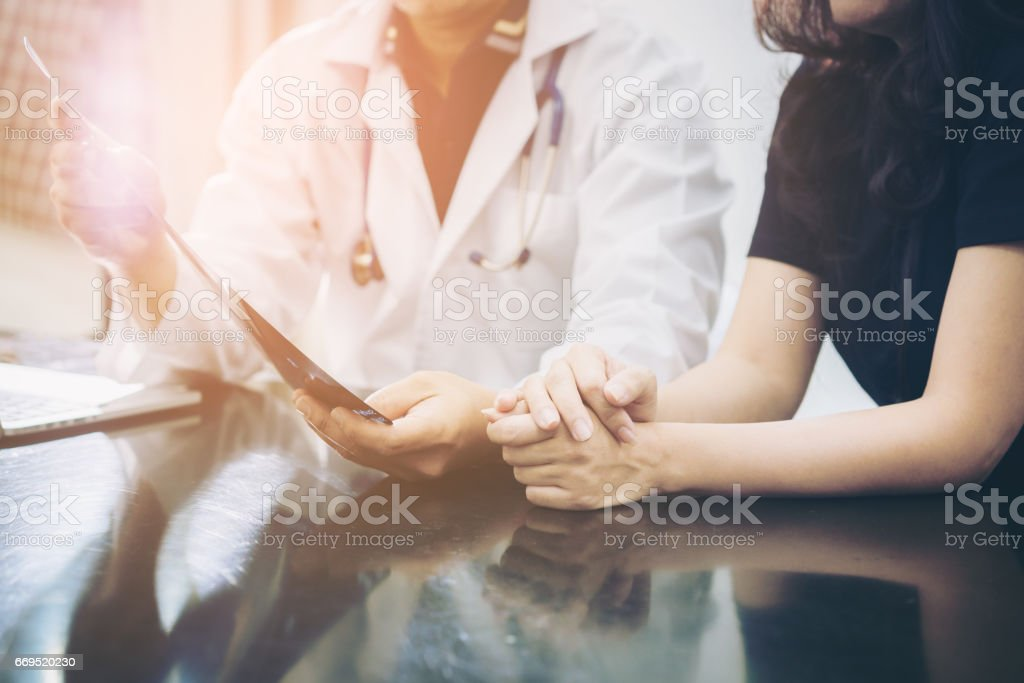 Doctor and patient consulting on a table stock photo