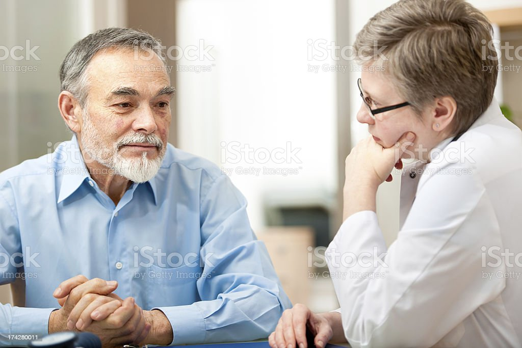 Doctor and patient deep in thought in a medical exam stock photo