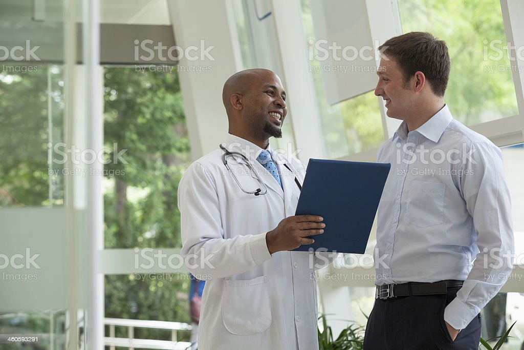 Doctor and patient discussing medical record in the hospital stock photo