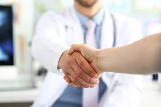 Doctor and patient handshake stock photo