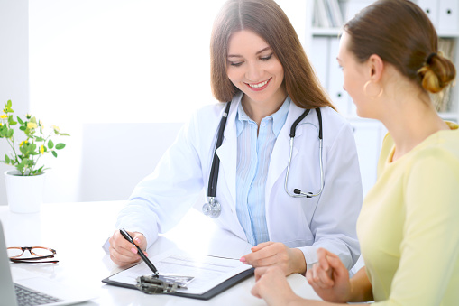 istock Doctor and  patient  have a talk while sitting at the desk near window 812444242