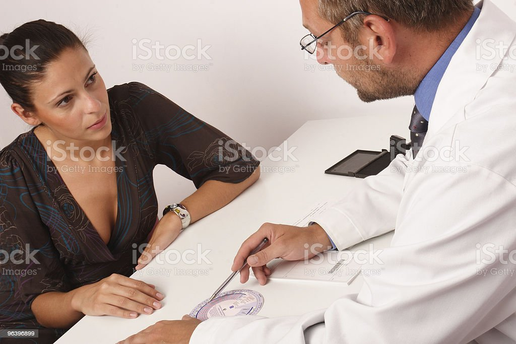 Doctor and patient having discussion at doctors office - Royalty-free Adult Stock Photo