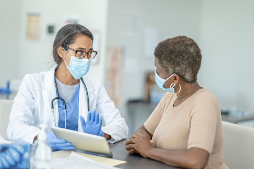 Female doctor and patient in personal protective equipment at medical exam.