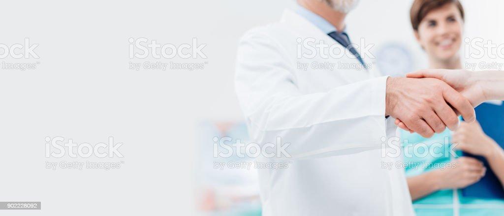 Médico e um paciente, apertando as mãos