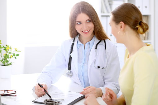 istock Doctor and  patient  sitting at the desk near window 697344994