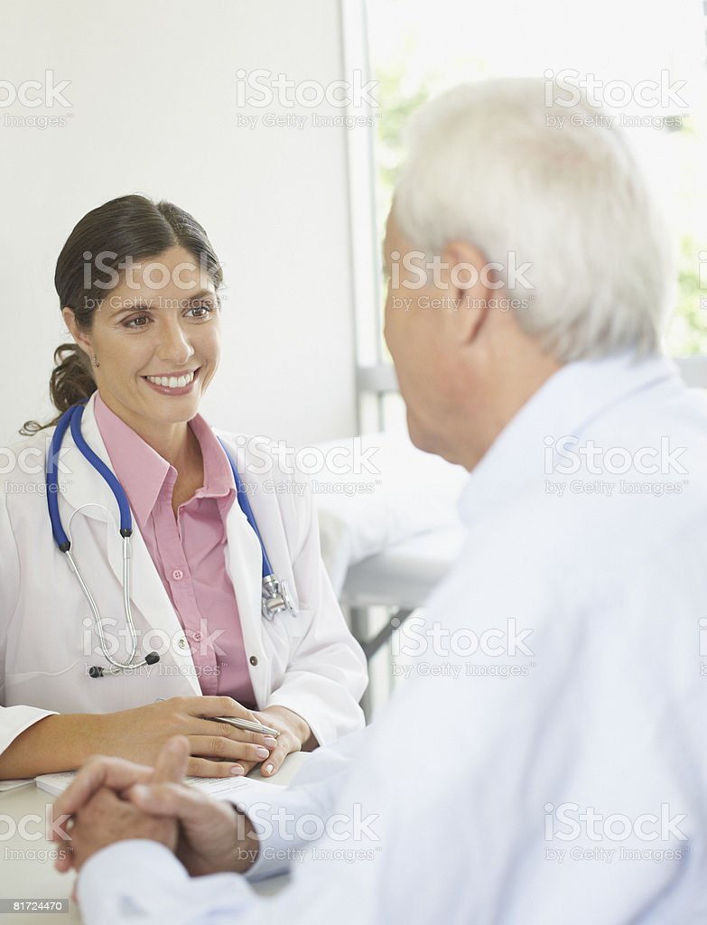 Doctor and patient sitting in office talking and smiling royalty-free stock photo