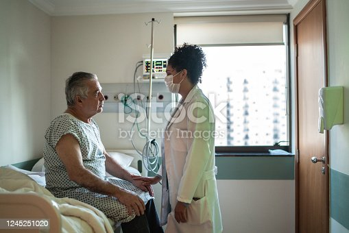 852092658 istock photo Doctor and patient talking at hospital room with face mask 1245251020