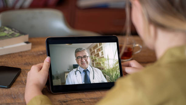 Doctor and patient talking on computer video call stock photo