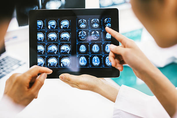 Doctor and patient using digital tablet in hospital stock photo