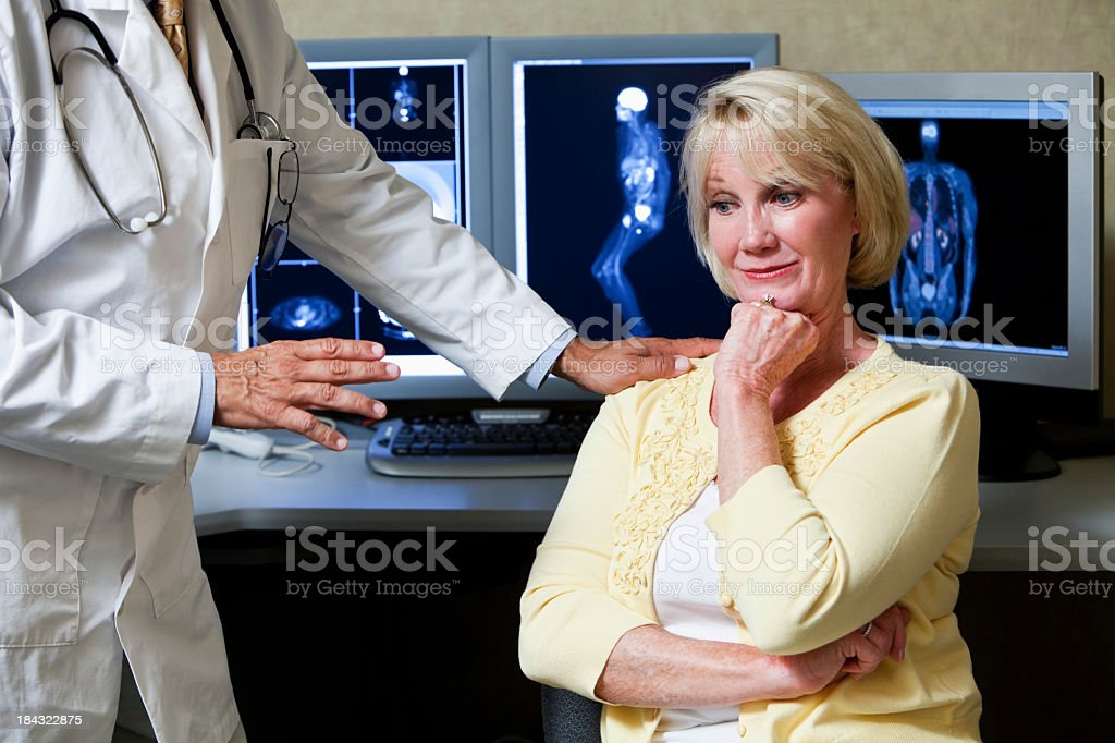 Doctor and patient with medical scans in background royalty-free stock photo