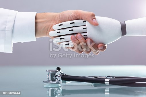 istock Doctor And Robot Shaking Hands 1013435444