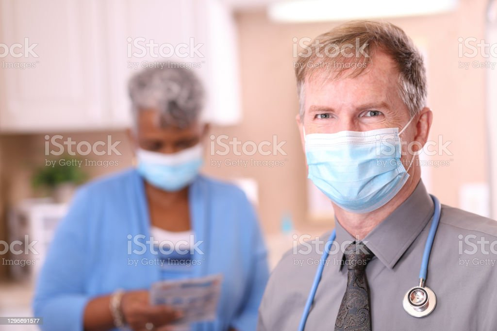 COVID-19: Doctor and senior adult, African descent patient, masks. Mature adult doctor or healthcare worker, consultation with senior adult, African American female patient in office, hospital, or clinic setting. Both wear protective face masks.  Coronavirus, medical exam, consultation. 70-79 Years Stock Photo
