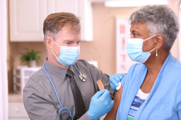 COVID-19: Doctor and senior adult, African descent patient, vaccine, masks. stock photo