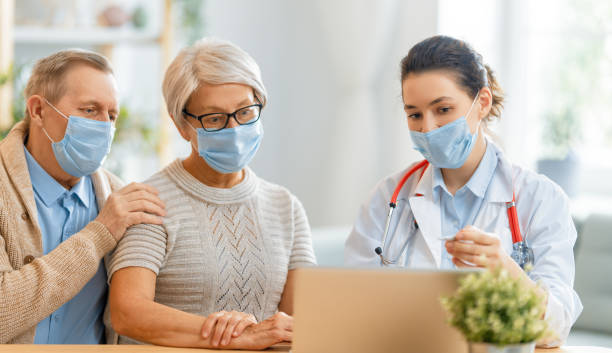 Doctor and senior couple wearing facemasks stock photo