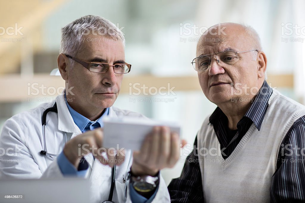 Doctor and senior man examining prescription medicine at doctor's office. stock photo