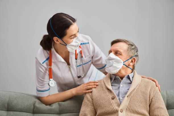 Doctor and senior man wearing facemasks stock photo