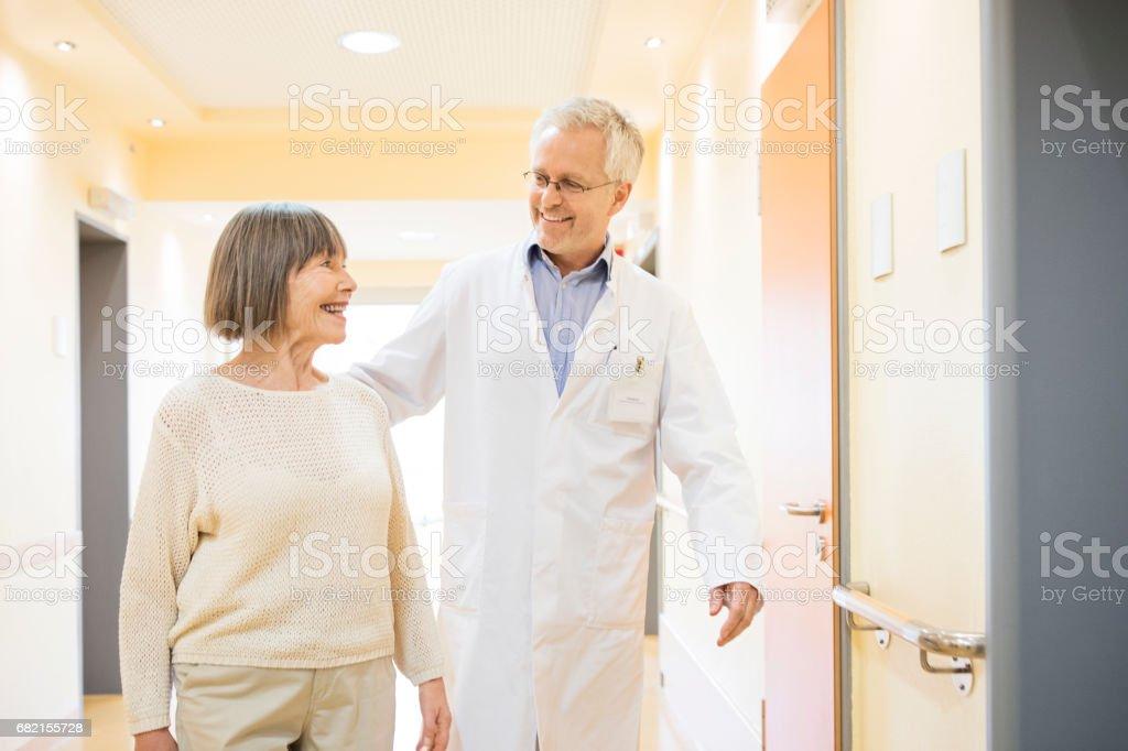 Arzt und Senior Patienten sprechen im Korridor – Foto