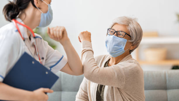 Doctor and senior woman wearing facemasks stock photo