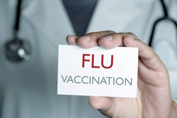 doctor and signboard with text flu vaccination stock photo