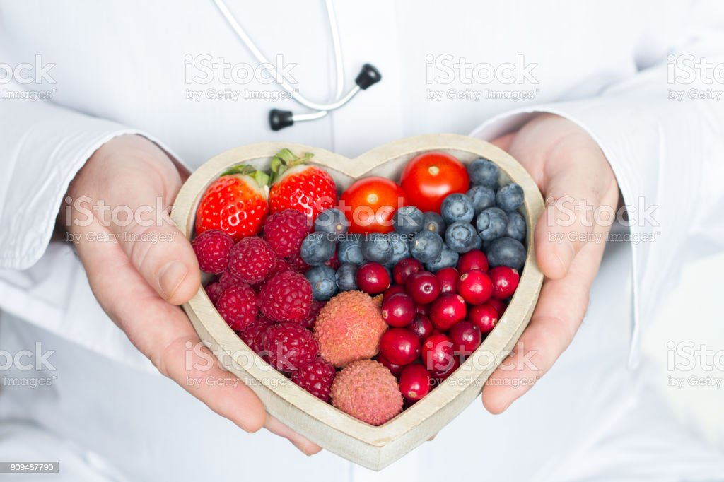 Doctor and stethoscope with heart healthy diet food abstract medicine concept stock photo