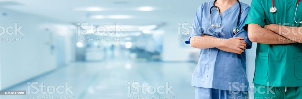Doctor and surgeon with arms crossed in hospital. stock photo