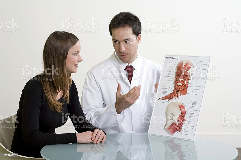 Doctor and woman planning cosmetic surgery at consultation stock photo