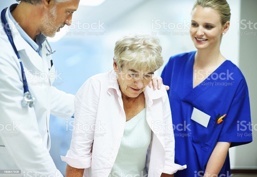 Doctor and young nurse helping a disabled woman royalty-free stock photo