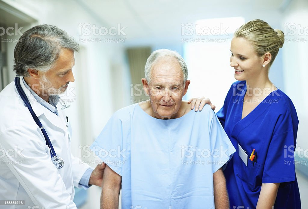 Doctor and young nurse with a disabled man royalty-free stock photo