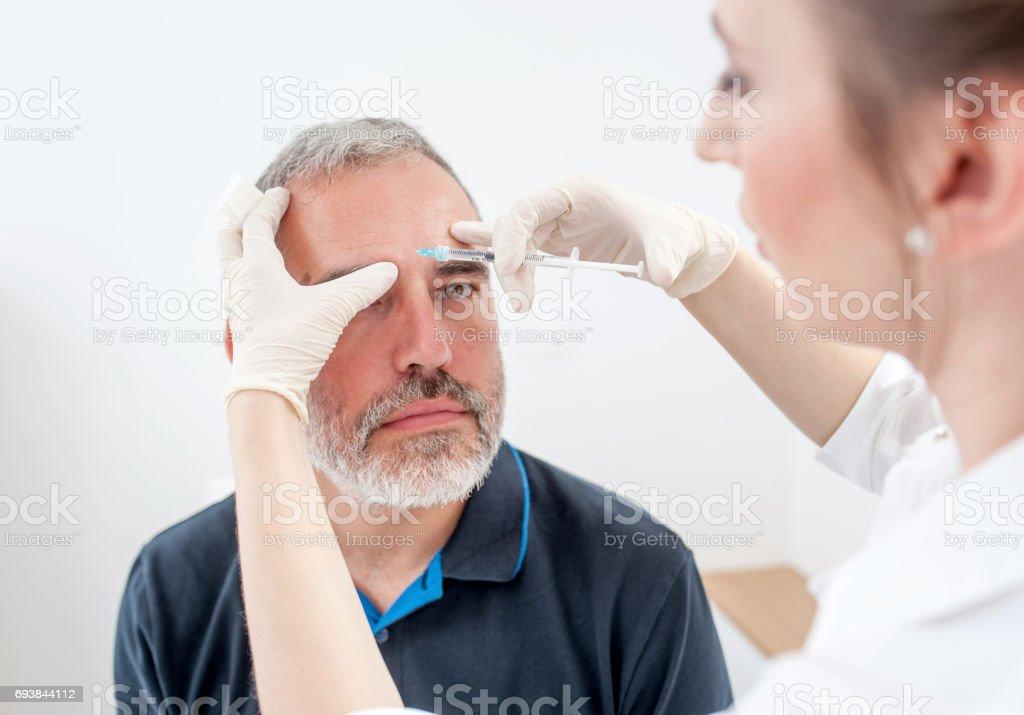 Läkare tillämpa Botox behandling på patientens ansikte bildbanksfoto