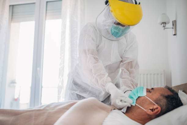 doctor applying face mask to a senior man who is lying in hospital bed because of coronavirus infection - indumento protettivo foto e immagini stock