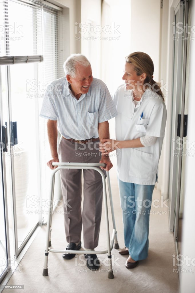 Doctor assisting an old man on a walker royalty-free stock photo