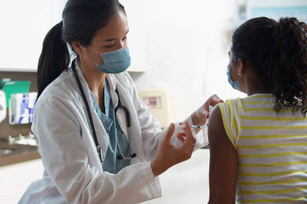 doctor at hospital wearing mask and giving patient injection