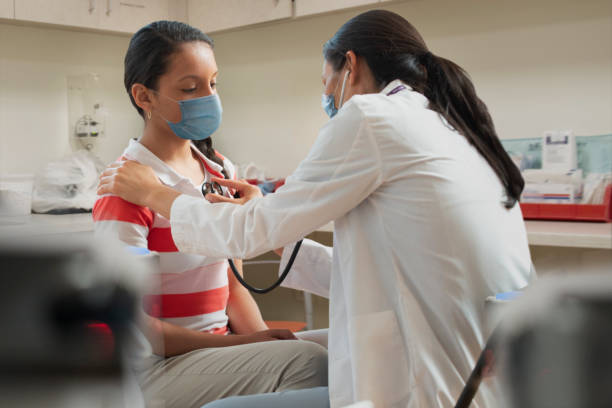 doctor at hospital wearing mask taking care of young patient